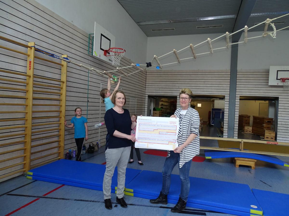 Antje Wiedmer vom Gewerbeverein Burgrieden-Achstetten übergibt die Spende an Annemone Hoffmann vom Förderverein der Grundschule Achstetten
